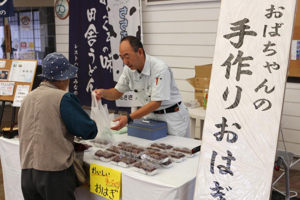 手作りおはぎの対面販売をするJA職員(右)HP